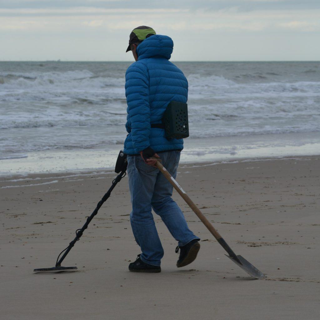 mand gaar med spade og metaldetektor paa stranden 1024x1024