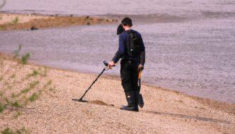 mand med spadeog metaldetektor paa stranden 332x190